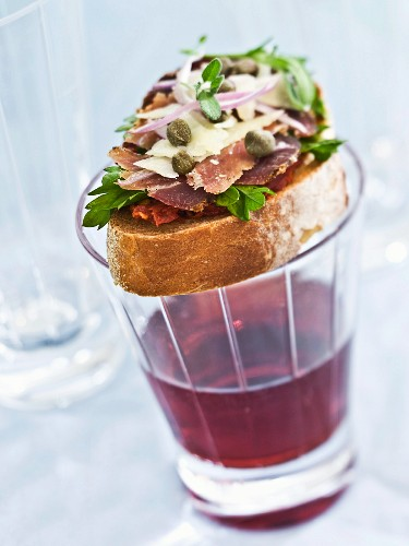 A slice of bread topped with ham, cheese and capers; served with a glass of red wine