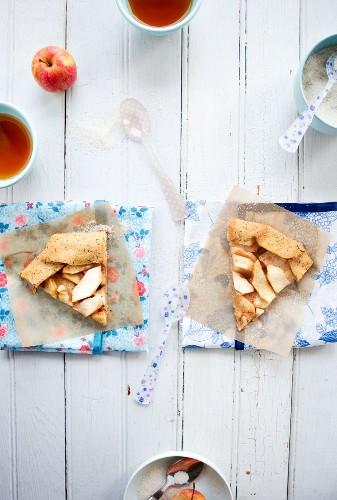Apple Tart Slices on Paper; Plastic Spoons
