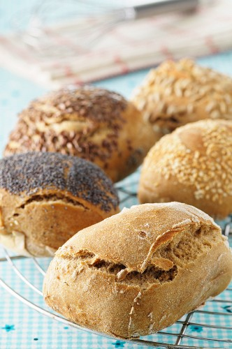 Assorted freshly baked rolls on a cooling rack