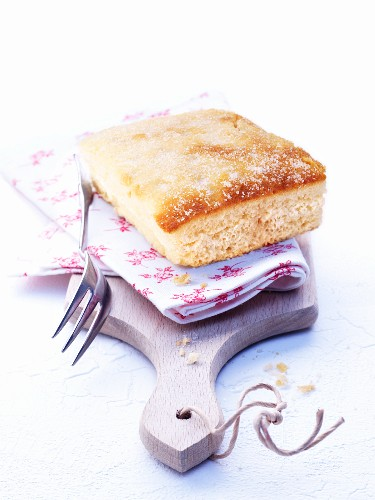 A piece of butter cake with a floral cloth on a chopping board