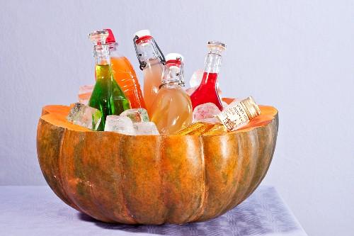 A hollowed out pumpkin as a bottle cooler