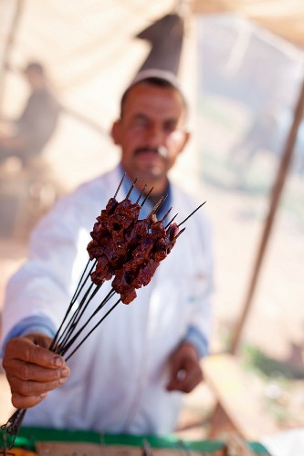 A shopkeeper demonstrating barbecued kebabs at a market (North Africa)