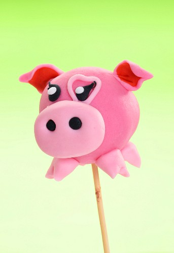 A cake pop decorated to look like a pig