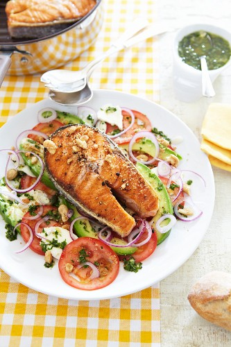Grilled salmon steak on a tomato and avocado salad