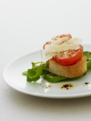 Grilled tomato on bruschetta with parmesan on a bed of spinach