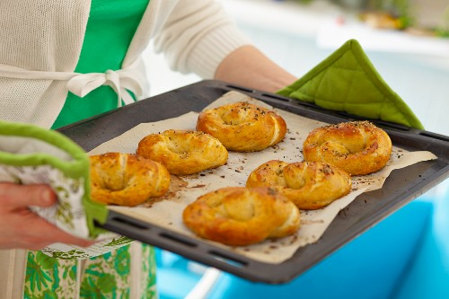Woman holding baking tray with freshly baked yeast pretzels