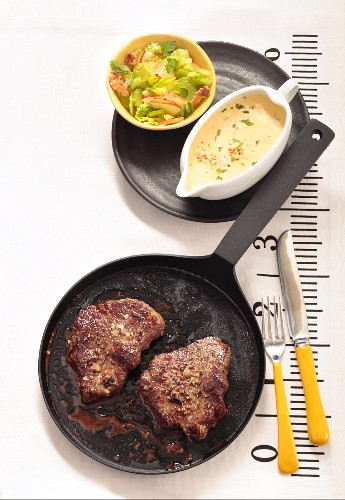 Beef steaks in the pan with bearnaise sauce and a side salad