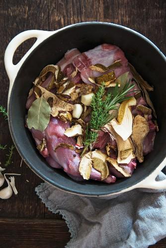 Rabbit, mushrooms, garlic and herbs in a casserole dish
