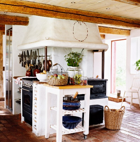 Chopping block table next to rustic kitchen cooker in Scandinavian country house