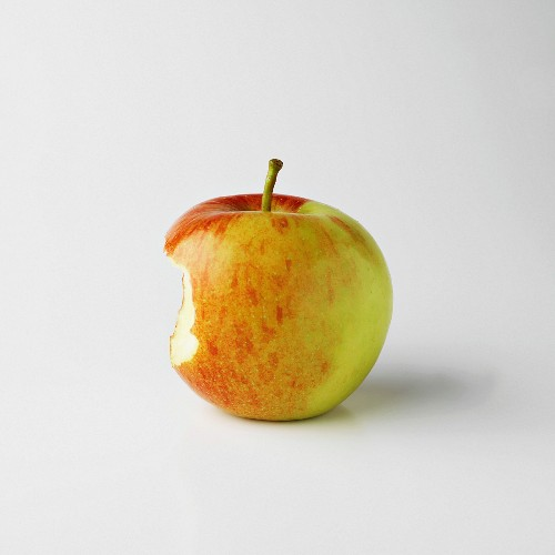 One apple on white background with bite mark