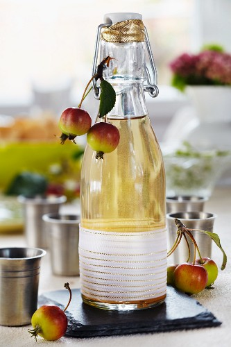 Apple liqueur in a decorative flip top bottle with ornamental apples and small pewter mugs next to it