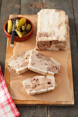 Pâté with chicken liver, partly sliced, and a small bowl of pickled gherkins
