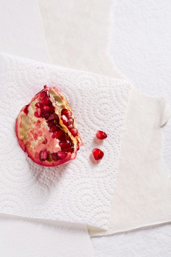 A chunk of pomegranate and pomegranate seeds on kitchen paper