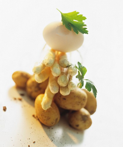 A still life of ingredients featuring white asparagus, potatoes and an egg