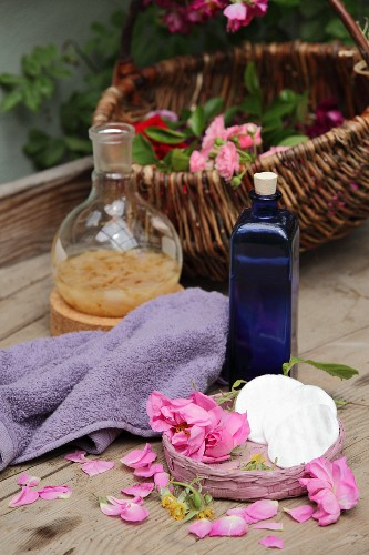An arrangement of home-made rosewater in a blue bottle next to a towel, roses and rose petals