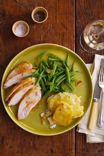 A Plate of Sliced Roast Chicken, Green Beans and Potato Gratin