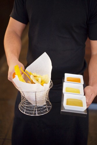 A Waiter Holding a Basket of Fried Plantain Chips with a Tray of Dipping Sauces