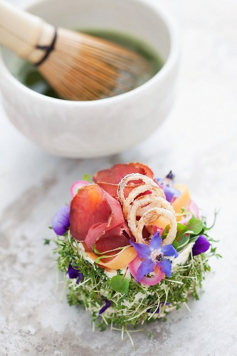 A canapé of bread topped with cream cheese, smoked elk, onions and borage flowers