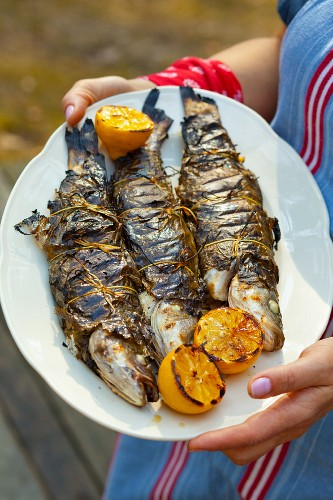 Grilled trout wrapped in vine leaves
