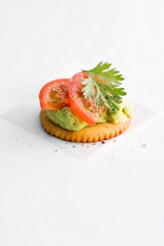A cracker topped with avocado pur