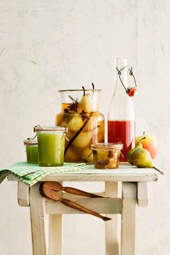A still life featuring spiced pears, baked apple jam, apple jelly and apple and cinnamon syrup