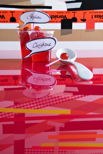 Cocktail cherries in beakers with name tags and white china spoon on red, reflective glass surface