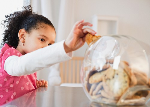 Hispanic girl taking cookie from jar