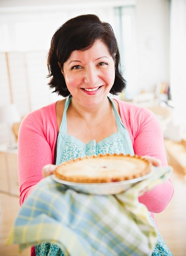 Hispanic woman holding out homemade pie
