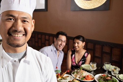 A chef and guests in a restaurant