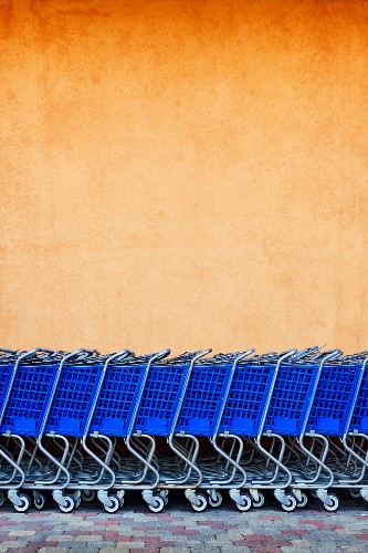 Line of Blue Shopping Carts Against Colorful Wall