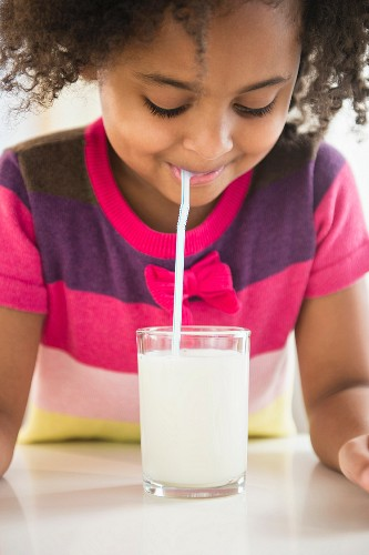 An African-American girl drinking a glass of milk through a straw