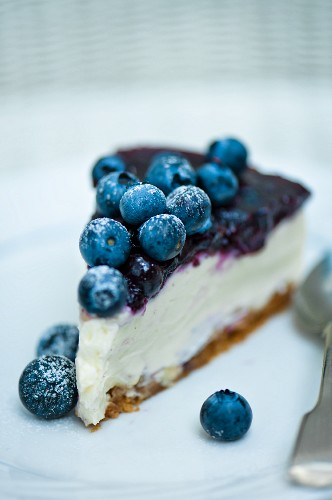a slice of blueberry cheesecake with a spoon