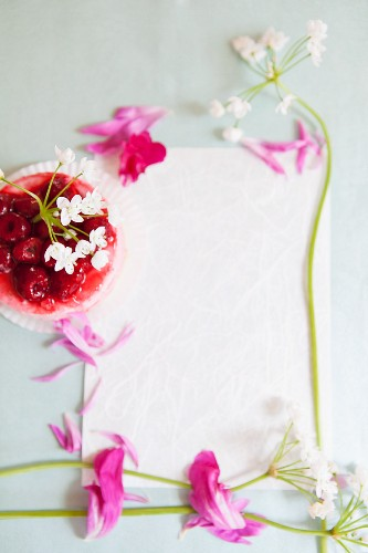 Raspberry jelly and flowers decorating the edge of a piece of paper