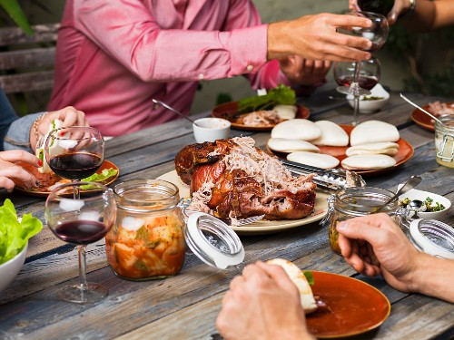 Friends enjoying roast pork with rolls, salad, kimchi and red wine at a garden table