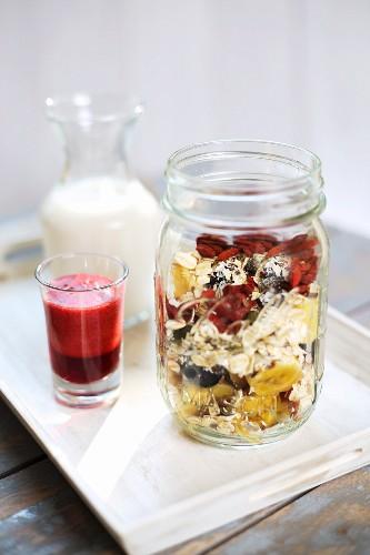 Breakfast parfait with goji berries, bananas, cashew nuts, milk and raspberry sauce