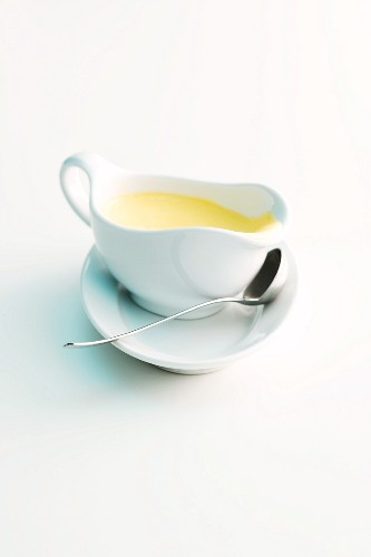 Sauce Hollandaise in a gravy boat with a ladle