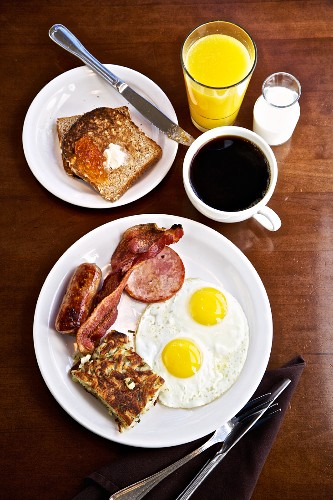 An American breakfast with two fried eggs, sausage and bacon