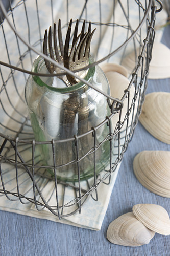 Silver forks in glass in wire basket