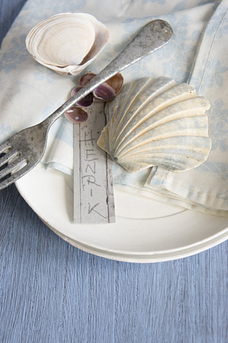 Place settings with silver fork, seashells and name tag