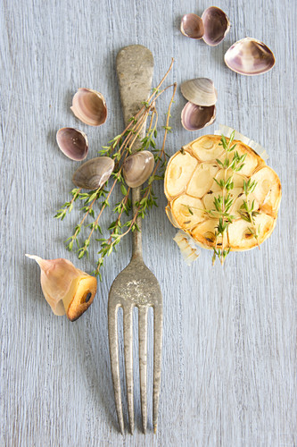 Roasted garlic, a silver fork and small shells