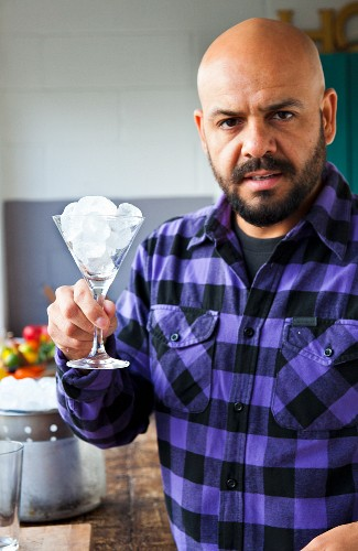 A barkeeper holding a cocktail glass filled with ice cubes