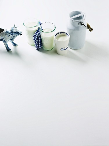 Three glasses of milk, a milk can and a cow figurine