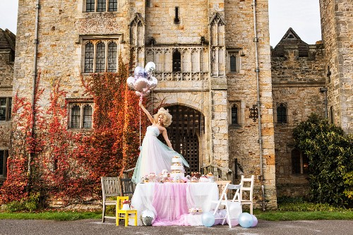 Bride holding balloons standing on festively set table in front of manor house