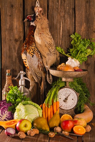 An autumnal arrangement featuring pheasants, vegetables, fruit, nuts and an old pair of kitchen scales