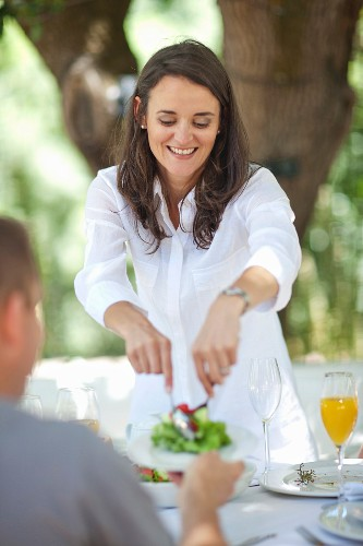 A smiling woman serving salad