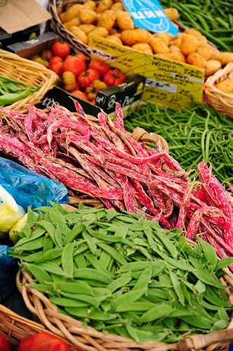 Mange tout, beans, tomatoes and potatoes on a market stand