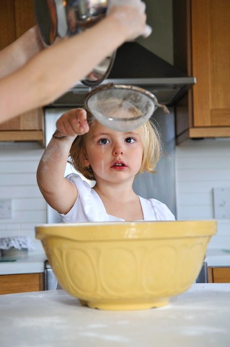 A little girl in a kitchen helping with baking