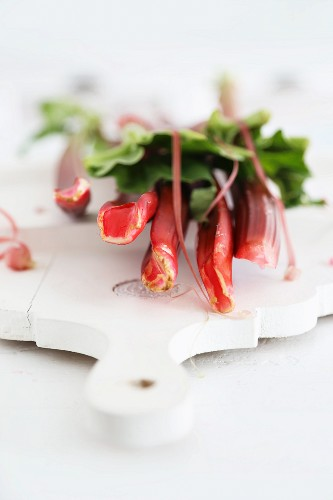 Stems of rhubarb on a white chopping board