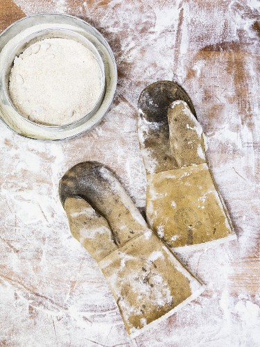 Oven gloves for bread baking on a wooden table