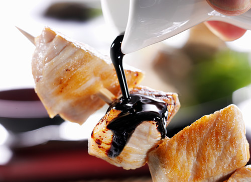 Soy sauce being poured over a chicken skewer (close-up)